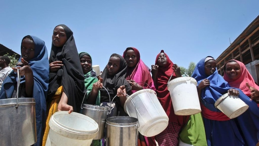 FILE - In this Saturday, Feb. 25, 2017 file photo, displaced Somali girls who fled the drought in southern Somalia stand in a queue to receive food handouts at a feeding center in a camp in Mogadishu, Somalia. Somalia's prime minister said Saturday, March 4, 2017 that 110 people have died from hunger in the past 48 hours in a single region as a severe drought threatens millions of people. (AP Photo/Farah Abdi Warsameh, File)