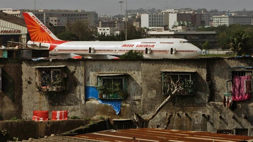 FILE- In this May 25, 2010 file photo, an Air India plane is seen in the background of slums adjoining the the international airport in Mumbai, India. Air India says it has set a world record by flying around the world with an all-female crew. Press Trust of India reported that the flight flew over the Pacific Ocean from New Delhi to San Francisco on Monday, and then flew back to New Delhi over the Atlantic on Friday. (AP Photo/Rajanish Kakade, file)
