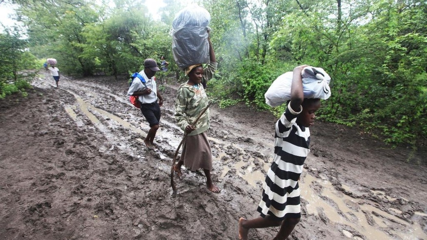 Villagers carry food for people taking care o of their livestock in Tsholostho about 200 kilometres north of Bulawayo, Saturday, March 4, 2017. Zimbabwe says floods have killed over 200 people and left close to 2,000 homeless since December. The Southern African country has appealed to International donors for $100 million to help those affected by floods. (AP Photo/ Tsvangirayi Mukwazhi)