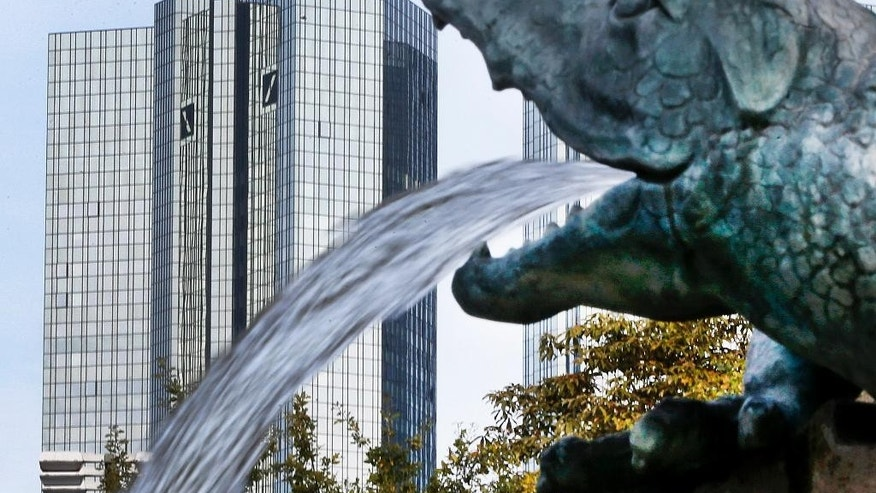 FILE - In this Oct. 11, 2016 file photo, water spills out of a small dragon sculpture on a fountain with the headquarters of the Deutsche Bank in background in Frankfurt, Germany,  Deutsche Bank says it is planning a capital increase to raise 8 billion euros (US $8.45 billion). The German lender said in a statement Sunday March 5, 2017 that the capital increase will come through the issuance of up to 687.5 million new shares (AP Photo/Michael Probst,file)