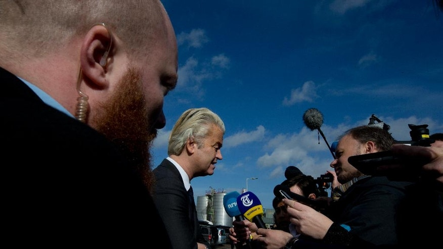 A body guard watches over firebrand anti Islam lawmaker Geert Wilders, center, as he answers questions during an election campaign stop at De Telegraaf newspaper in Amsterdam, Netherlands, Sunday, March 5, 2017. (AP Photo/Peter Dejong)
