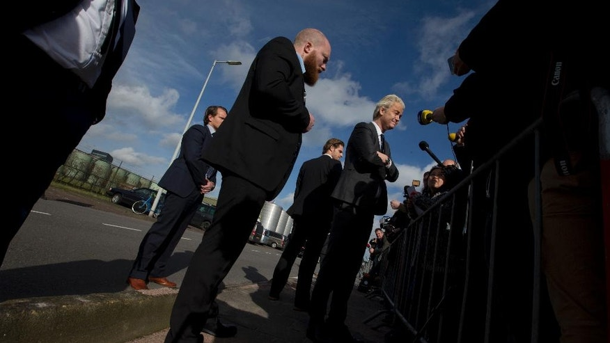 Security guards watch over firebrand anti Islam lawmaker Geert Wilders, center right, as he answers questions during an election campaign stop at De Telegraaf newspaper in Amsterdam Netherlands, Sunday, March 5, 2017. (AP Photo/Peter Dejong)
