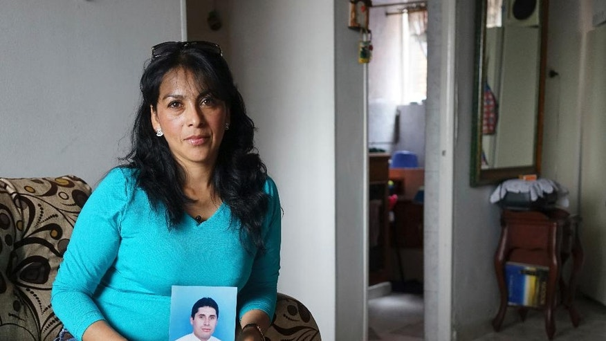 In this March 1, 2017 photo, Martha Antivar holds a portrait of her husband Oscar Hilarion in her mother-in-law's apartment in Bogota, Colombia. Five years ago, Hilarion told his family he was going to China on a business venture. Weeks later Antivar learned her husband had been detained for trafficking drugs, a desperate act she believes he committed in order to stop the bank from seizing their home. (AP Photo/Christine Armario)