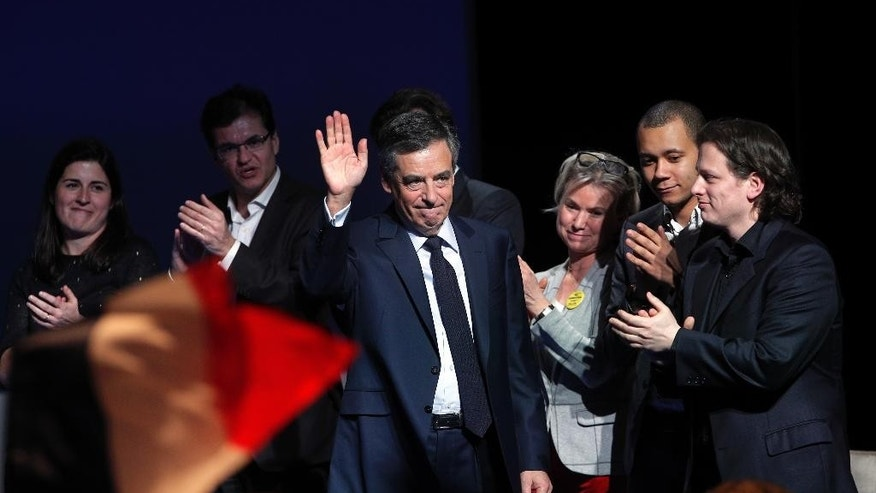 Conservative presidential candidate Francois Fillon waves as he arrives to deliver his speech during a campaign meeting in Aubervilliers, outside Paris, France, Saturday, March 4, 2017. Fillon, whose campaign has been unraveling over impending corruption charges, vowed to remake France in a speech on Saturday, a day before what amounts to his last stand, a rally near the Eiffel Tower widely seen as a test of his staying power via the number of supporters he can muster. (AP Photo/Christophe Ena)