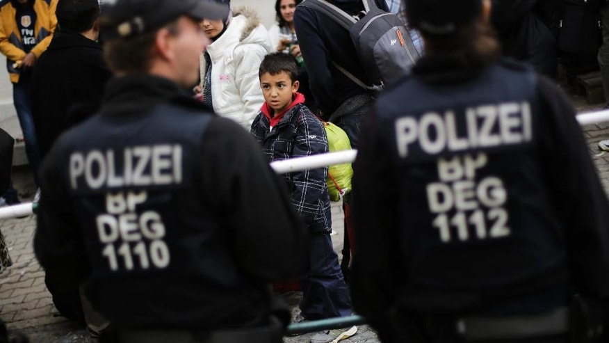 "FILE - In this Sept. 16, 2015 file photo, a young boy looks at police officers after he and other migrants were pulled out of a train by German Federal Police at the train station of the southern German border town Passau,   German newspaper 'Welt am Sonntag' reports that the government planned to close the border with Austria and turn back asylum-seekers in September 2015, but nixed the plan at the last minute., the paper reported Sunday March 5, 2017.  The interior ministry said in a statement it could ""neither confirm nor deny"" the report.  (AP Photo/Markus Schreiber,file)"