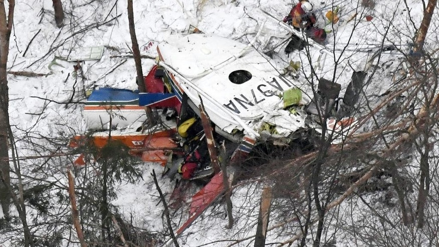 Rescuers work near the helicopter crashed in mountains in Nagano prefecture, central Japan Sunday, March 5, 2017. The rescue helicopter carrying nine people has crashed in snow-coved mountains during a training flight. (Daisuke Suzuki/Kyodo News via AP)