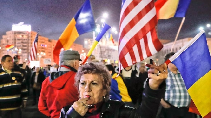 A protester blows a whistle as others shout anti-government slogans during a rally in Bucharest, Romania, Sunday, March 5, 2017. Thousands marched through the Romanian capital to show support for the country's anti-corruption authority, the DNA, demanding the state's institutions operate free from political influences. (AP Photo/Vadim Ghirda)
