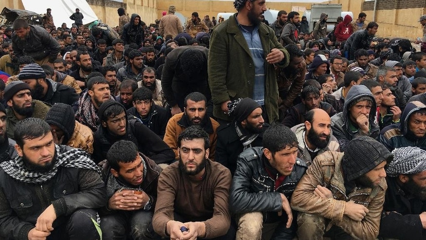 Displaced men who fled their homes due to fighting between Iraqi security forces and Islamic State militants wait for security check at an Iraqi Army base, west of Mosul, Iraq, Saturday, March 4, 2017. (AP Photo/Mohammed Numan)