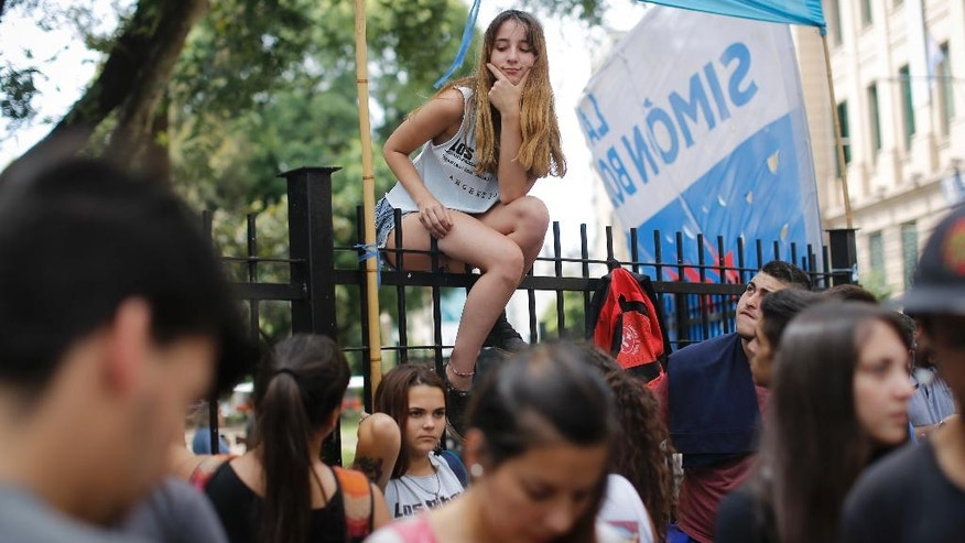 A high school student protesting along with teachers sit atop a fence in Buenos Aires, Argentina, Monday, March 6, 2017. Teachers in a nationwide strike have left millions of children without classes in the first serious union conflict for president's Mauricio Macri's administration. (AP Photo/Victor R. Caivano)
