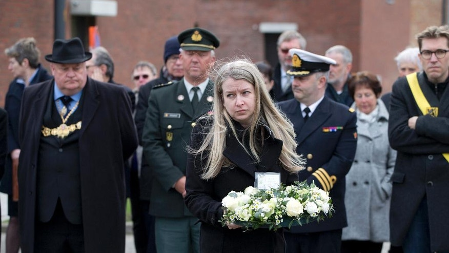 Kim Spooner, center, from Britain, carries flowers for an uncle she lost during a remembrance service for the the victims of the Herald of Free Enterprise in Zeebrugge, Belgium on Sunday, March 5, 2017. On March 6, 2017, thirty years will have passed since the ferry Herald of Free Enterprise capsized with the loss of 193 lives shortly after setting out to Dover from the Belgian port of Zeebrugge. (AP Photo/Virginia Mayo)