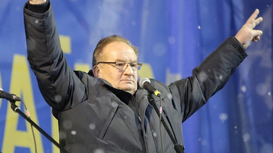 FILE - In this Dec. 7, 2013 file photo, Jacek Saryusz-Wolski, vice president of the European People's Party and chairman of the European People's Party Group, cheers pro-European Union supporters at a mass rally in the Independence Square as snow falls in Kiev, Ukraine. Saryusz-Wolski is Poland's surprise counter-candidate to challenge incumbent Donald Tusk for the post of European Council head.  (AP Photo/Efrem Lukatsky, File)
