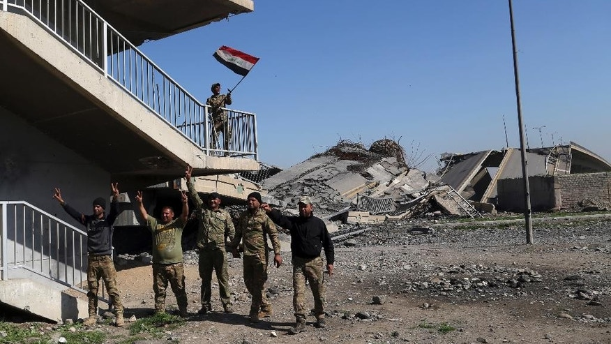 Iraqi soldiers celebrate on a bridge that they recently regained control of, from Islamic State militants, in western Mosul, Iraq, Monday, March 6, 2017. (AP Photo/Khalid Mohammed)
