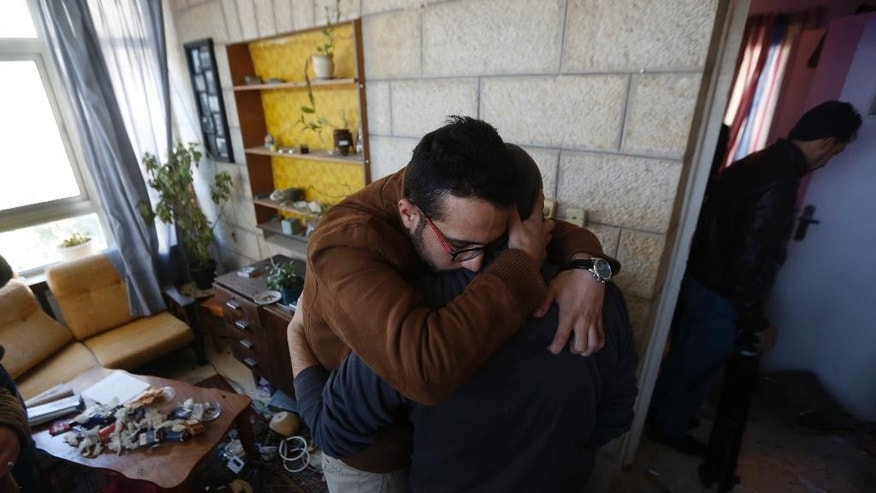 Man embrace inside the house of Basil al-Araj in the West Bank city of Ramallah, Monday, March 6, 2017.Police say Israeli forces early Monday entered the Ramallah area in the West Bank to arrest 31-year-old Palestinian militant al-Araj, and he opened fire, leading to a shootout that killed him. (AP Photo/Majdi Mohammed)