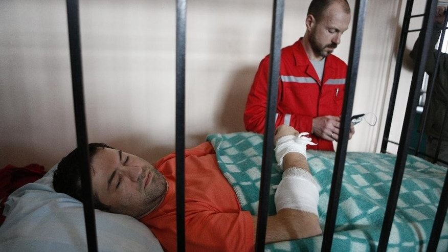 Head of Ukraine's State Fiscal Service Roman Nasirov, lays in a bed behind the bars with a medical worker in the background, during a court session in Kiev, Ukraine, Saturday, March 5, 2017. Nasirov was detained earlier this week on corruption charges. (AP Photo/Sergei Chuzavkov)