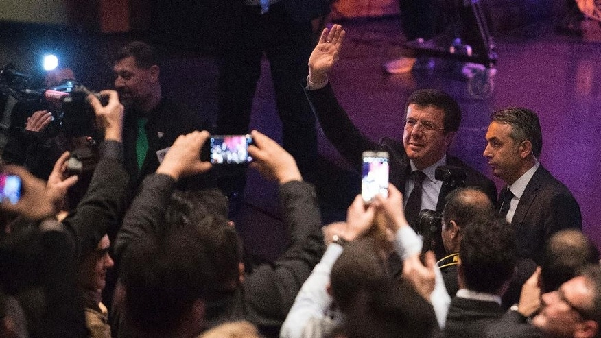 Turkish Minister for Economic Affairs, Nihat Zeybekci, second right,  waves as he arrives at the forum hall in Leverkusen, Germany, Sunday, March 5, 2017. (Marius Becker/dpa via AP)