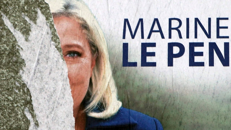 FILE - In this Dec. 11, 2015 file photo, a defaced poster of French far-right party leader Marine Le Pen is seen in Henin-Beaumont, northern France.
