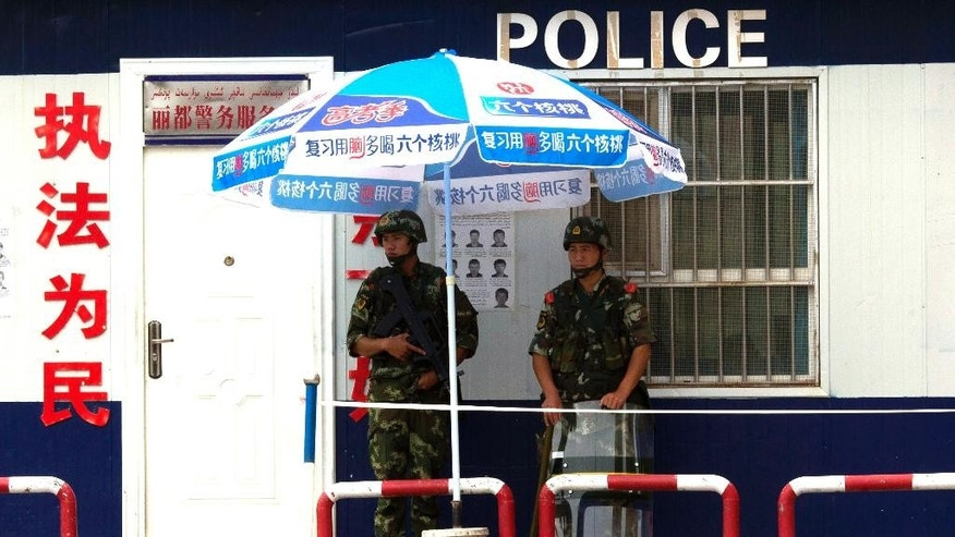FILE - In this July 17, 2014 file photo, armed Chinese paramilitary policemen stand on duty near wanted posters at a check point in Aksu in western China's Xinjiang province. A notice Tuesday, March 7, 2017 on the website of the government of Kashgar city in Xinjiang offered high salaries and other benefits to recruit police in the restive region that has seen bloody attacks blamed on separatists. (AP Photo/Ng Han Guan, File)