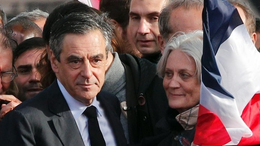 "French conservative presidential candidate Francois Fillon and his wife Penelope appear during a rally in Paris, Sunday, March 5, 2017. Fillon is urging his supporters not to ""give up the fight"" for the presidency despite corruption allegations dogging him. (AP Photo/Christophe Ena)"