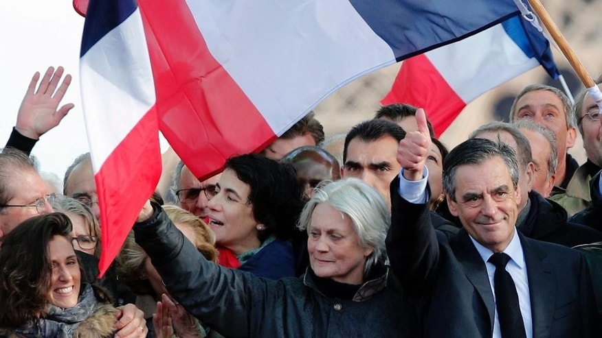 "French conservative presidential candidate Francois Fillon, right, thumbs up with his wife Penelope after delivering his speech during a rally in Paris, Sunday, March 5, 2017. Fillon is urging his supporters not to ""give up the fight"" for the presidency despite corruption allegations dogging him. (AP Photo/Christophe Ena)"