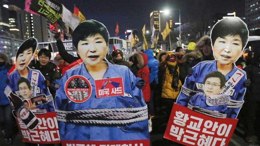 FILE - In this Jan. 14, 2017, file photo, protesters hold cutouts of impeached President Park Geun-hye who is embroiled in a corruption scandal, during a protest in Seoul, South Korea. A survey by the anti-graft group Transparency International shows that bribery and other forms of corruption are hindering poverty alleviation and hurting public health by channeling resources away from those who need them. The survey, released Tuesday, March 7, 2017, estimated that more than 900 million people in the region had paid bribes in the past year to obtain basic public services like schooling and health care. (AP Photo/Ahn Young-joon, File)
