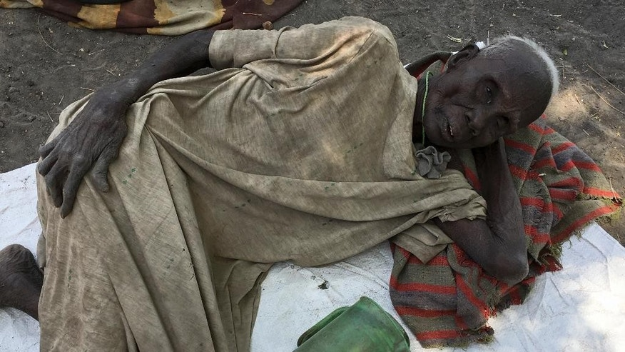In this photo taken Wednesday, March 1, 2017, Juang Gai Vol, 87, who hadn't eaten for three days, lies down at a food distribution site in Padeah, South Sudan. South Sudanese who fled famine and fighting in Leer county emerged from South Sudan's swamps after months in hiding to receive food aid being distributed by the World Food Program. (AP Photo/Sam Mednick)