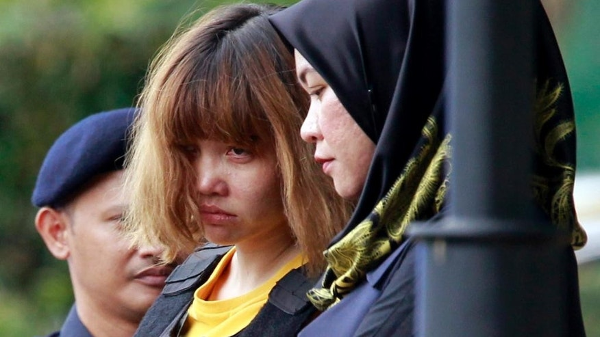 FILE - In this Wednesday, March 1, 2017, file photo, Vietnamese suspect Doan Thi Huong, center, in the ongoing assassination investigation, is escorted by police officers out from Sepang court in Sepang, Malaysia. Two of the world's most intriguing mysteries are in the hands of Malaysian investigators. One of them _ the fatal poisoning of a relative of North Korea's ruler _ happened long after the other _ Malaysia Airlines Flight 370, which vanished three years ago Wednesday. Authorities have more evidence in the killing of Kim Jong Nam than in the plane disappearance, but both cases may prove impossible to solve completely. (AP Photo/Daniel Chan, File)