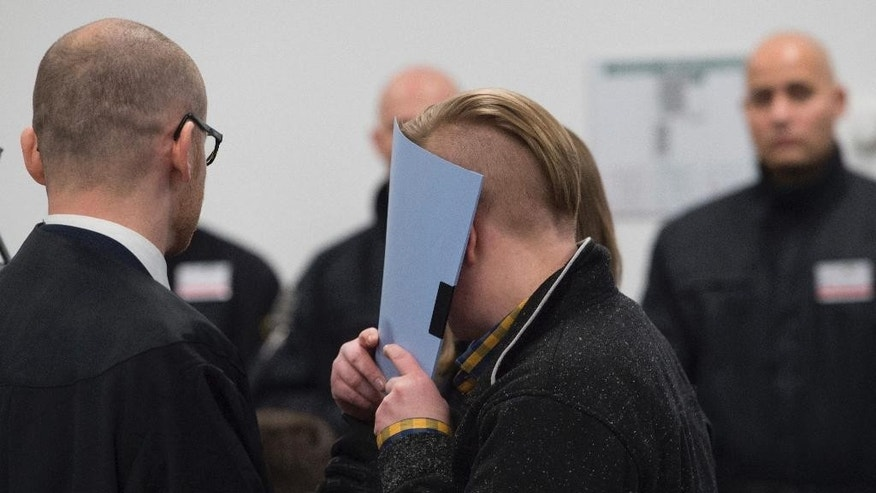 The accused Maria K. center, enters the hearing room of the correctional facility at the beginning of the trial in Dresden, Germany, Tuesday, March 7, 2017. Eight Germans are going on trial for allegedly forming a far-right terrorist organization and carrying out bombing attacks on asylum-seeker facilities and left-wing political targets. (Sebastian Kahnert/dpa via AP)