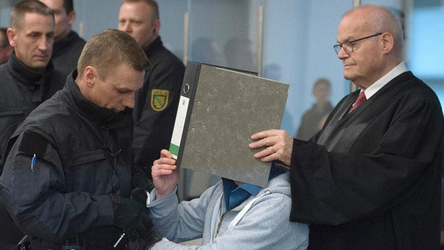 The accused Justin S., center, is led into the hearing room of the correctional facility by judiciary officials at the beginning of the trial in Dresden, Germany, Tuesday, March 7, 2017. Eight Germans are going on trial for allegedly forming a far-right terrorist organization and carrying out bombing attacks on asylum-seeker facilities and left-wing political targets. (Sebastian Kahnert/dpa via AP)