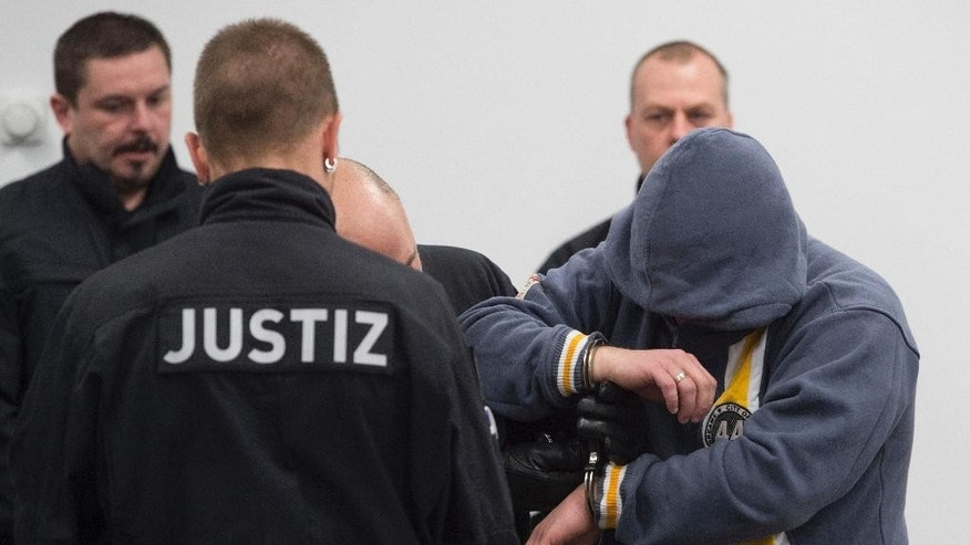 The accused Mike S., right, enters the hearing room of the correctional facility at the beginning of the trial in Dresden, Germany, Tuesday, March 7, 2017. Eight Germans are going on trial for allegedly forming a far-right terrorist organization and carrying out bombing attacks on asylum-seeker facilities and left-wing political targets. (Sebastian Kahnert/dpa via AP)