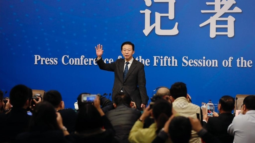 Chinese Finance Minister Xiao Jie waves as he arrives for a press conference on the sideline of the National People's Congress at the media center in Beijing, Tuesday, March 7, 2017.  China's finance minister is rejecting accusations that the country is keeping its defense budget under wraps.  Xiao's remarks came after China released its national budget without the usual figure for defense spending. (AP Photo/Andy Wong)