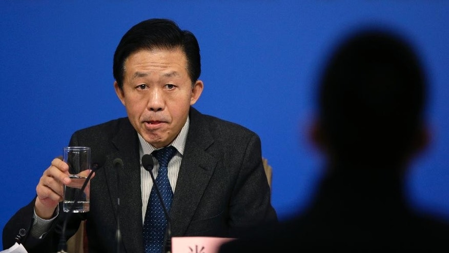 Chinese Finance Minister Xiao Jie pauses while listening a question from a journalist during a press conference on the sideline of the National People's Congress at the media center in Beijing, Tuesday, March 7, 2017.  China's finance minister is rejecting accusations that the country is keeping its defense budget under wraps.  Xiao's remarks came after China released its national budget without the usual figure for defense spending.  (AP Photo/Andy Wong)