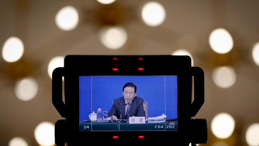 Chinese Finance Minister Xiao Jie is displayed on a camera monitor during a press conference on the sideline of the National People's Congress at the media center in Beijing, Tuesday, March 7, 2017.  China's finance minister is rejecting accusations that the country is keeping its defense budget under wraps.  Xiao's remarks came after China released its national budget without the usual figure for defense spending. (AP Photo/Andy Wong)