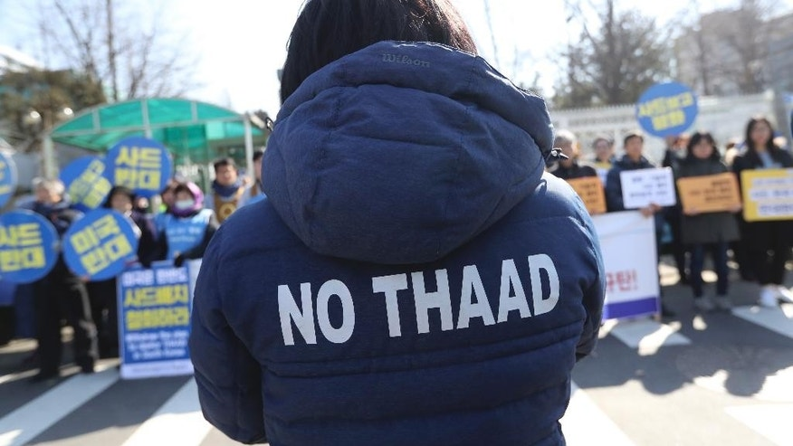 "A protester wearing a jacket with ""No THAAD"" letters, participates during a rally to oppose the plan to deploy the Terminal High-Altitude Area Defense system, or THAAD, in front of the Defense Ministry in Seoul, South Korea, Tuesday, March 7, 2017. U.S. missile launchers and other equipment needed to set up a controversial missile defense system have arrived in South Korea, the U.S. and South Korean militaries said Tuesday, a day after North Korea test-launched four ballistic missiles into the ocean near Japan. (AP Photo/Lee Jin-man)"