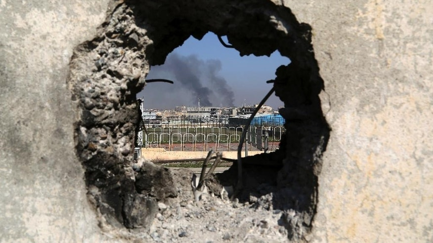 Smoke rises from government complex, seen through a hole in a wall that made by Iraqi forces to fire their weapons, as Iraqi security forces advance during fighting against Islamic State militants in western Mosul, Iraq, Tuesday, March 7, 2017. U.S.-backed Iraqi forces were fighting their way through a government complex in the heart of western Mosul after storming the buildings in an overnight raid, and were facing fierce counterattacks Tuesday from the Islamic State group. (AP Photo/Khalid Mohammed)