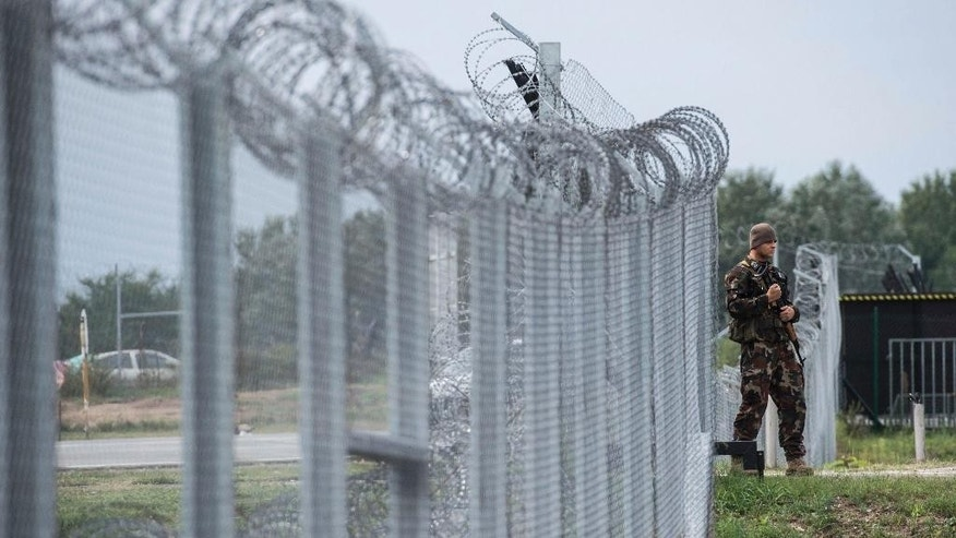 FILE - In this Sept. 21, 2016 file photo a Hungarian soldier patrols at the transit zone at Hungary's southern border with Serbia near Tompa, 169 km southeast of Budapest, Hungary. Hungary's Prime Minister Viktor Orban, an early supporter of U.S. President Donald Trump, has ordered the reinforcement of fences on Hungary's southern borders to keep out migrants, many of whom are Muslims. (Sandor Ujvari/MTI via AP, file)