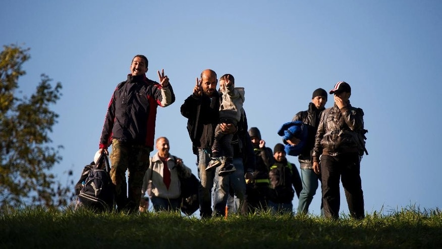 FILE - In this Oct. 20, 2015 file photo migrants cross the Austrian - Slovenian border in Spielfeld, Austria. Austria was among the first countries in Europe to put out the welcome mat to migrants when the first waves of people fleeing war and poverty reached the continent. Now, its focus is showing them the door.  Parliament is set to pass a law stripping denied asylum-seekers of pocket money, food and shelter, potentially leaving them on the street. (AP Photo/Christian Bruna, file)