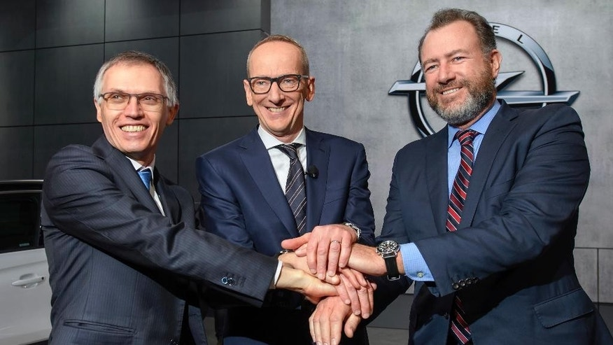 Carlos Tavares, left, CEO of PSA Peugeot Citroen, Karl-Thomas Neumann, center, CEO of Opel Group and President of General Motors Dan Ammann, right, shake hands during the press day at the 87th Geneva International Motor Show in Geneva, Switzerland, Tuesday, March 7, 2017. The Motor Show will open its gates to the public from March 9 to 19. (Martial Trezzini/Keystone via AP)