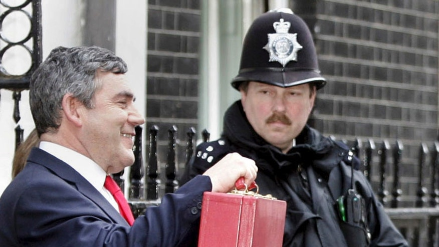 FILE - In this Wednesday March 16, 2005 file photo, Britain's Chancellor of the Exchequer Gordon Brown holds up his red budget box as he departs his official residence in Downing Street, London to deliver the annual budget. Brown, who was Chancellor for 10 years, became prime minister in 2007 butl asted only 3 years. The budget on Wednesday, March 8, 2017 to be delivered by Philip Hammond is set to be the final spring budget. (AP Photo /Adam Butler, File)