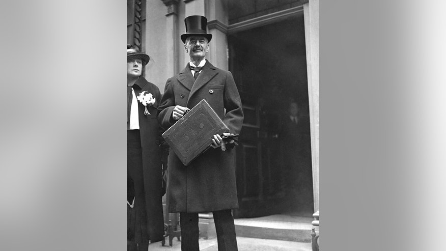 FILE - In this April 21, 1936 file photo, Britain's Chancellor of the Exchequer Neville Chamberlain  as he stands with his red budget box in London. Chamberlain, who would go onto be prime minister at the outbreak of World War II, was Chancellor for years during the Great Depression. The budget on Wednesday, March 8, 2017 to be delivered by Philip Hammond is set to be the final spring budget. (AP Photo, File)