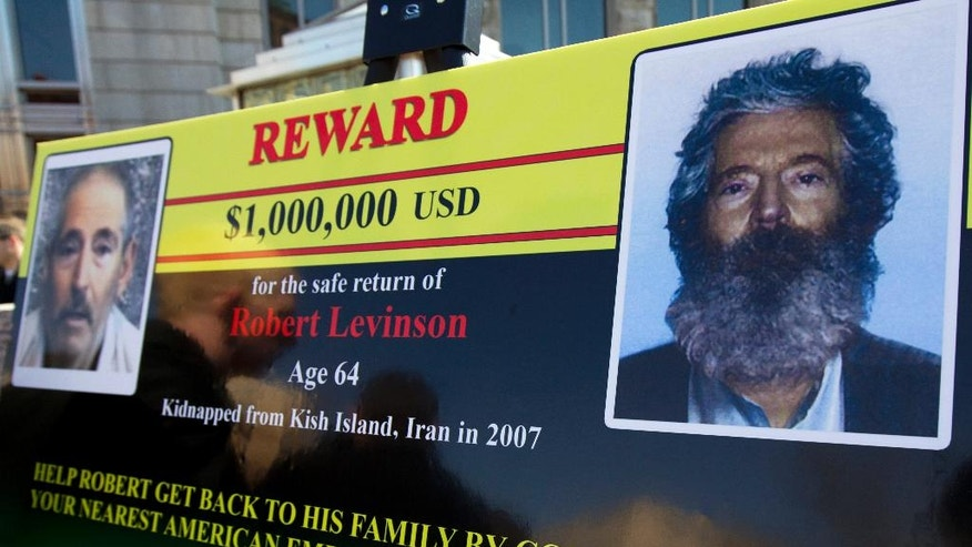 FILE- In this Tuesday, March 6, 2012 file photo, an FBI poster showing a composite image of former FBI agent Robert Levinson, right, of how he would look like now after five years in captivity, and an image, left, taken from the video, released by his kidnappers, in Washington during a news conference. It's been 10 years since former FBI agent Robert Levinson disappeared while in Iran on an unauthorized CIA mission and his family is still waiting for answers. His family tells The Associated Press they hope the new administration of President Donald Trump will do more to find him. (AP Photo/Manuel Balce Ceneta, File)