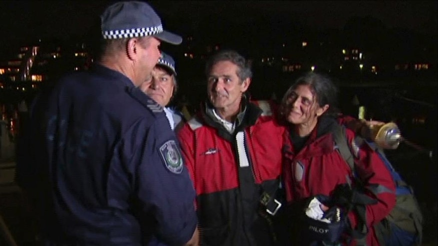 In this Wednesday, March 8, 2017 image made from video, Nick Dwyer, second right, and Barbara Heftman, right, thank police rescuers in Sydney after being rescued off Australia's southeastern coast. The Irishman and French woman have been rescued after their yacht's rudder broke in raging seas between Australia and New Zealand in the midst of the couple's around the globe voyage. (Australian Broadcasting Corporation via AP)