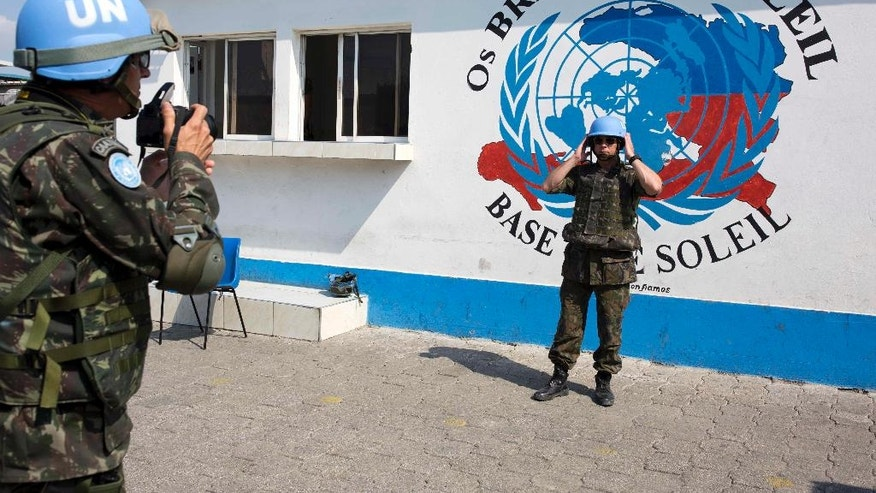 In this Feb. 22, 2017 photo, a U.N. peacekeeper from Brazil poses for a souvenir photo before the start of a patrol in the Cite Soleil slum, in Port-au-Prince, Haiti. With a steady downsizing of Haiti peacekeeping operations in recent years and the U.S. administration of President Donald Trump pushing for cutbacks, the U.N. is looking at sending home more than 2,000 troops from contributing countries. (AP Photo/Dieu Nalio Chery)