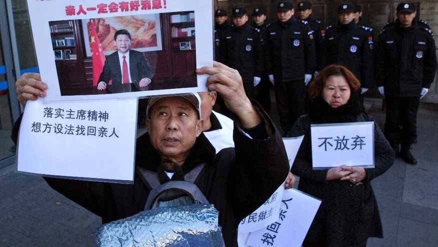 "Relatives of passengers onboard the missing Malaysia Airlines Flight 370 demand for the Chinese government to continue the search, with banners showing Chinese President Xi Jinping and the words ""Don't Give Up"" near the Foreign Ministry in Beijing, China, Wednesday, March 8, 2017. Wednesday marked the third anniversary of the disappearance of MH370, which vanished March 8, 2014 while en route from Kuala Lumpur to Beijing. (AP Photo/Ng Han Guan)"