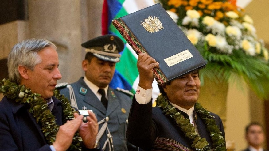 Bolivia's President Evo Morales holds up the folder containing the newly-signed coca law at the presidential palace in La Paz, Bolivia, Wednesday, March 8, 2017. Morales, who was rushed last week to Cuba for emergency treatment for problems with his vocal chords, reappeared Wednesday and against all recommendations spoke for almost an hour in defense of the controversial new law that would increase the amount of land for legal coca cultivation. Pictured left is Bolivia's Vice President Alvaro Garcia. (AP Photo/Juan Karita)