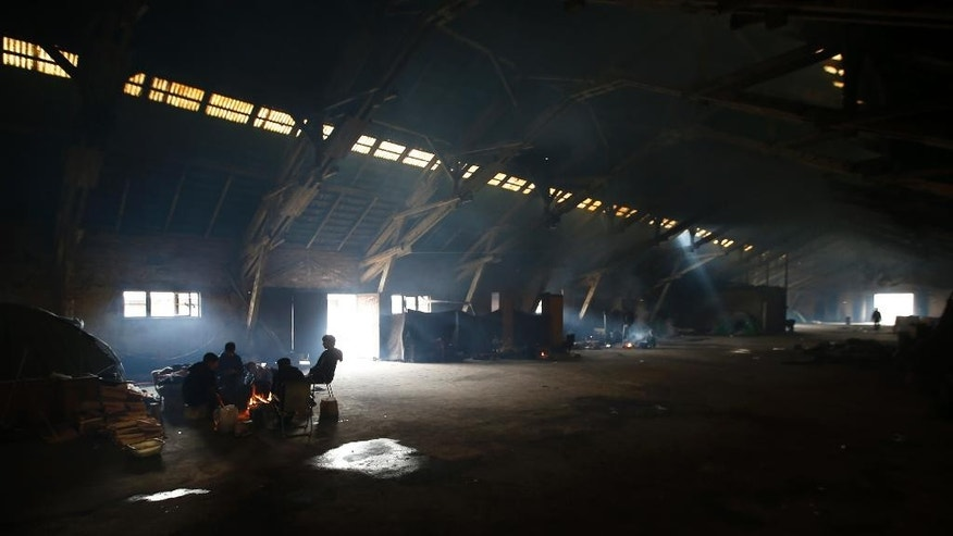Migrants gathered around the fire which they use for cooking and warmth inside a crumbling warehouse that has served as a make-shift shelter in Belgrade, Serbia, Tuesday, March 7, 2017. Migrants trying to reach the European Union from Serbia are worried because Hungary has imposed even tighter asylum rules for people fleeing war and poverty. (AP Photo/Darko Vojinovic)