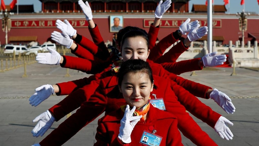 In this Sunday, March 5, 2017 photo, hospitality staff pose for photos on Tiananmen Square during the National People's Congress held at the Great Hall of the People in Beijing. Dressed in vermillion coats, colorful scarves and high-heeled boots, the well-coiffed young women accompany delegates to China's rubberstamp legislature to the Great Hall of the People then hold signs up to guide them back to their buses. In between, the women move on to the equally important tasks of taking selfies and posing for painstakingly composed group photos. (AP Photo/Andy Wong)