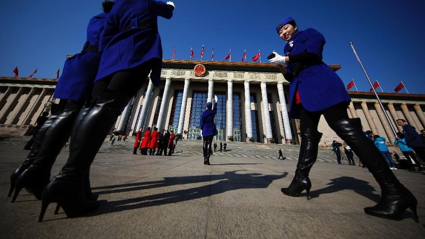 In this Sunday, March 5, 2017, photo, hospitality staff take souvenir photos in front of the Great Hall of the People where the National People's Congress is held in Beijing. Dressed in vermillion coats, colorful scarves and high-heeled boots, the well-coiffed young women accompany delegates to China's rubberstamp legislature to the Great Hall of the People then hold signs up to guide them back to their buses. In between, the women move on to the equally important tasks of taking selfies and posing for painstakingly composed group photos. (AP Photo/Andy Wong)