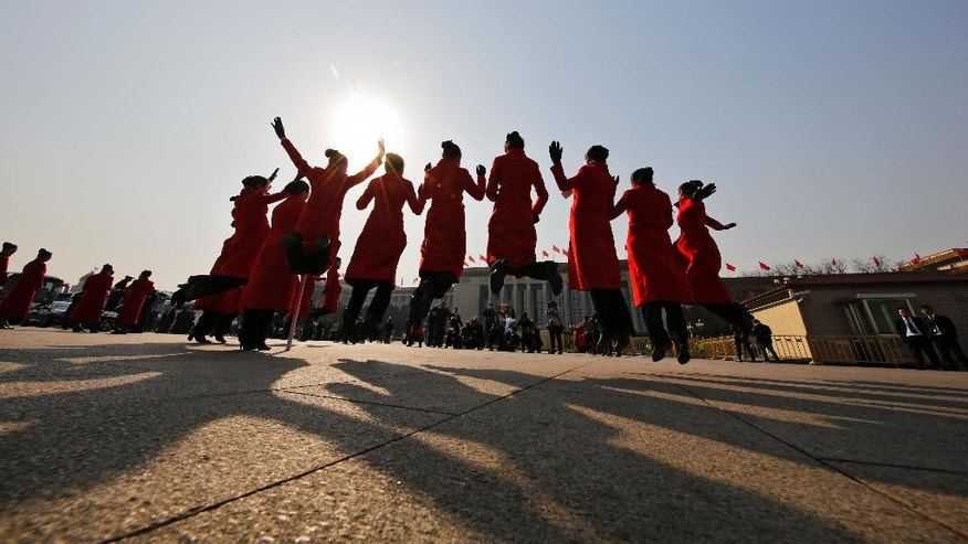 In this Friday, March 3, 2017 photo, hospitality staff jump as they pose for photographs on Tiananmen Square during the Chinese People's Political Consultative Conference (CPPCC) held at the Great Hall of the People in Beijing. Dressed in vermillion coats, colorful scarves and high-heeled boots, the well-coiffed young women accompany delegates to China's rubberstamp legislature to the Great Hall of the People then hold signs up to guide them back to their buses. In between, the women move on to the equally important tasks of taking selfies and posing for painstakingly composed group photos. (AP Photo/Andy Wong)