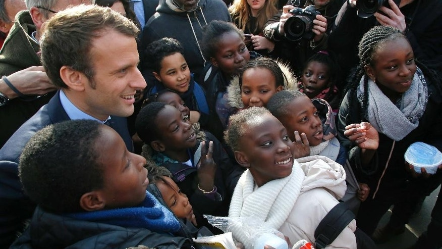 Independent centrist presidential candidate Emmanuel Macron poses with students of the Moliere school for a group photo in Les Mureaux, west of Paris, France, Tuesday, March 7, 2017. The first French presidential ballot will take place on April 23 and the two top candidates go into a runoff on May 7. (AP Photo/Michel Euler)