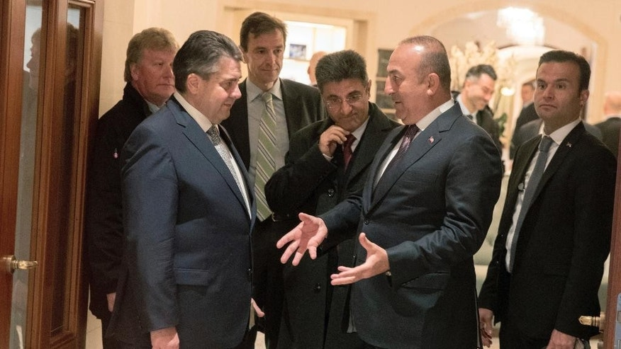 German Foreign Minister Sigmar Gabriel, left, talks to his Turkish counterpart Mevlut Cavusoglu, second right, after a meeting in a hotel in Berlin, Wednesday, March 8, 2017. (Kay Nietfeld/dpa via AP)